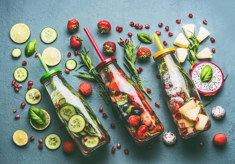 Flat lay of colorful infused water in bottles with fruits berries, cucumber, herbs and drink straws with ingredients on table, top. View. Tasty summer clean royalty free stock images