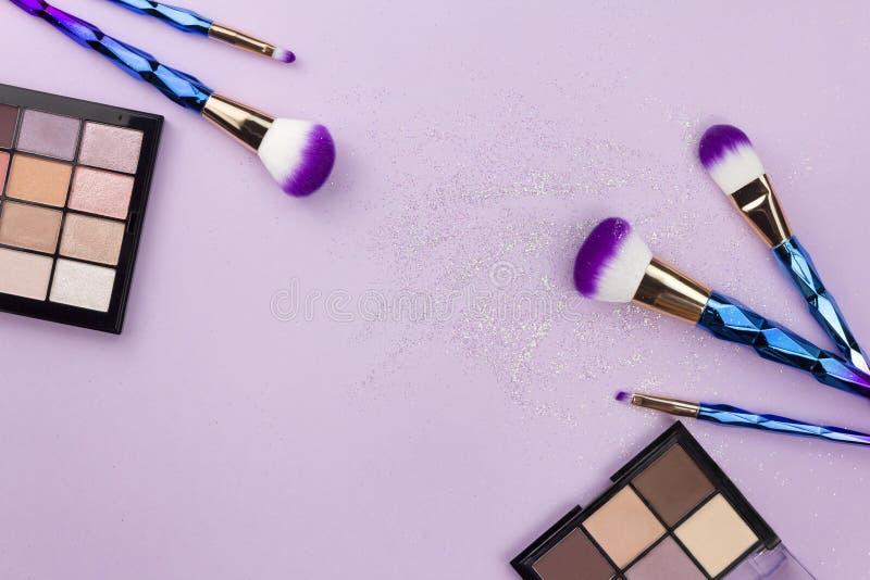 Flat lay colorful make up set with unicorn glitter on pastel purple background royalty free stock image