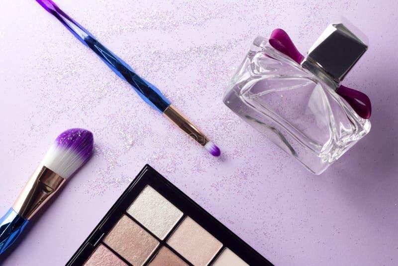 Flat lay colorful make up set with unicorn glitter on pastel purple background stock photos