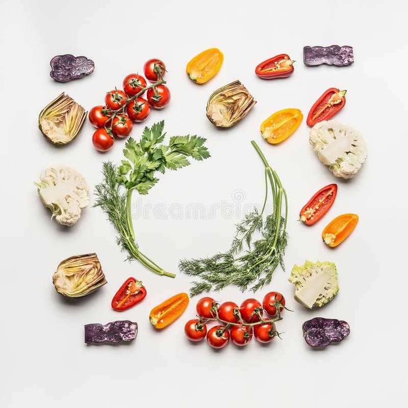 Flat lay of colorful salad vegetables ingredients with seasoning on white background, top view, frame. Healthy clean eating royalty free stock photography