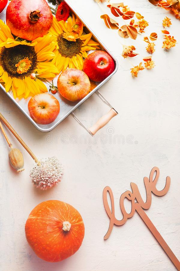 Flat lay composing with apples and sunflowers in tray on white table with pumpkin and autumn leaves and word love sign. Autumn. Love. Copy space for your design stock photo