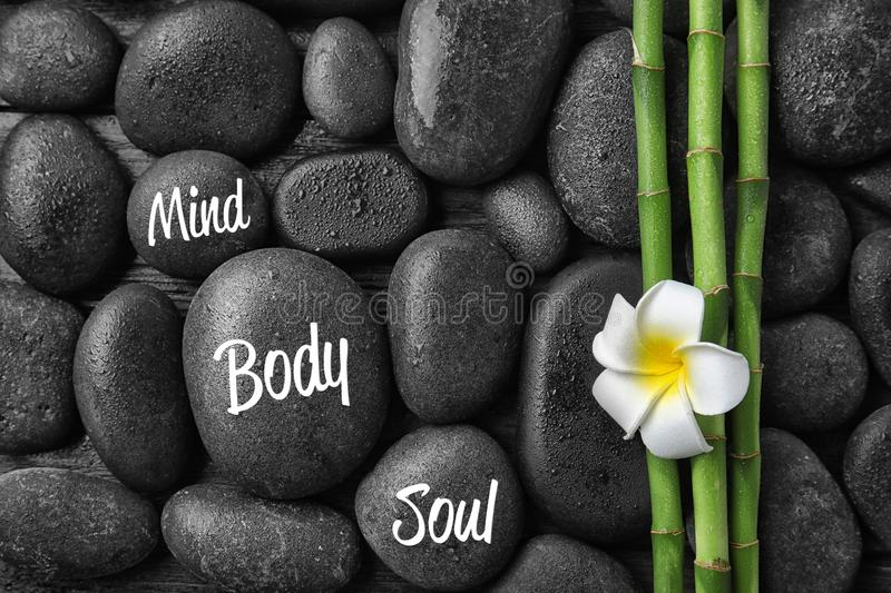 Flat lay composition with bamboo branches and spa stones as background. royalty free stock photo