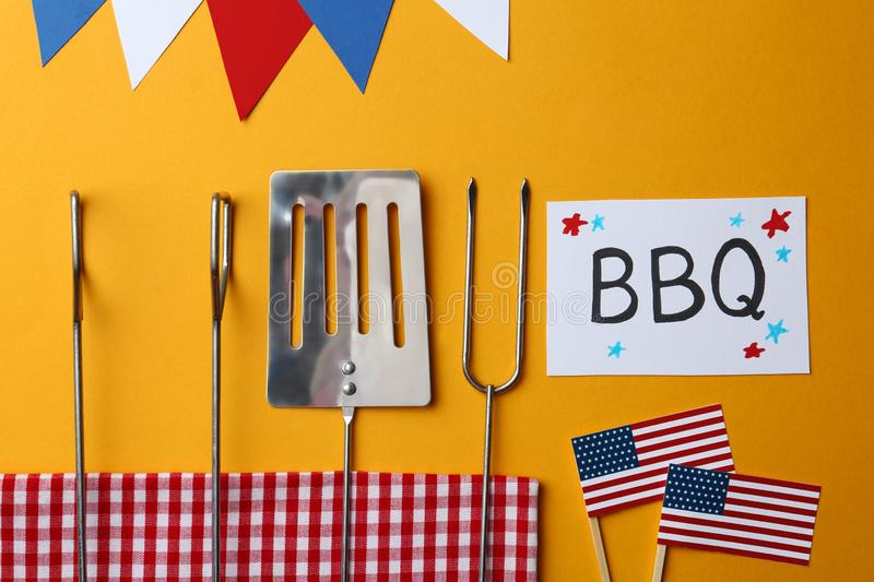 Flat lay composition with barbecue tools and card. USA Independence Day. Flat lay composition with barbecue tools and card on color background. USA Independence stock photo