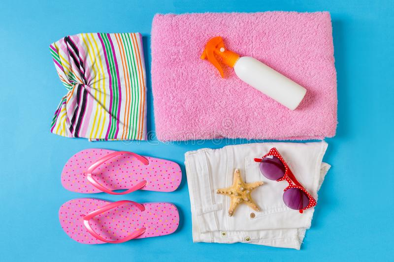 Flat lay composition with Beach accessories on blue color background. Summer holiday background. Vacation and travel items top stock photography