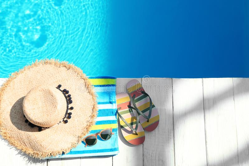 Flat lay composition with beach accessories on wooden deck near swimming pool. Space for text royalty free stock photos