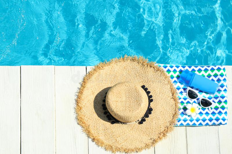 Flat lay composition with beach accessories on wooden deck near swimming pool. Space for text royalty free stock image