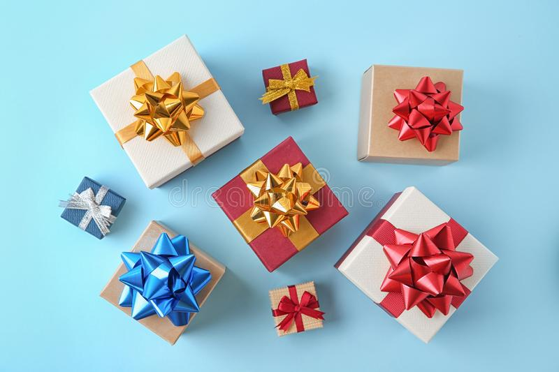 Lay composition with beautiful gift boxes on blue background. Flat lay composition with beautiful gift boxes on blue background royalty free stock images