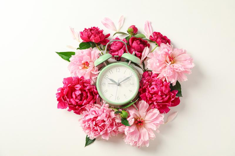 Flat lay composition with beautiful peonies and alarm clock on white background. Space for text royalty free stock photo