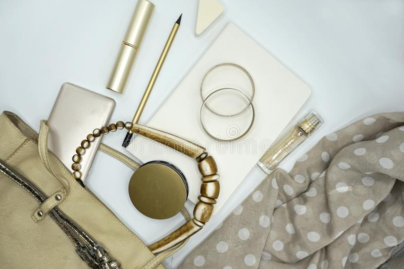 Flat lay composition of beauty products and handbag for women. Pastel and gold colors on white background. royalty free stock photos