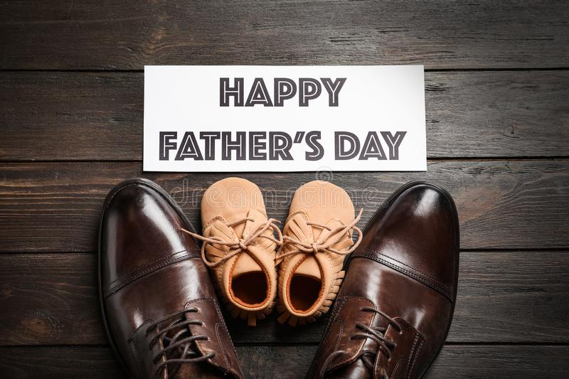 Flat lay composition with big and small shoes. On wooden background. Father`s day celebration stock images