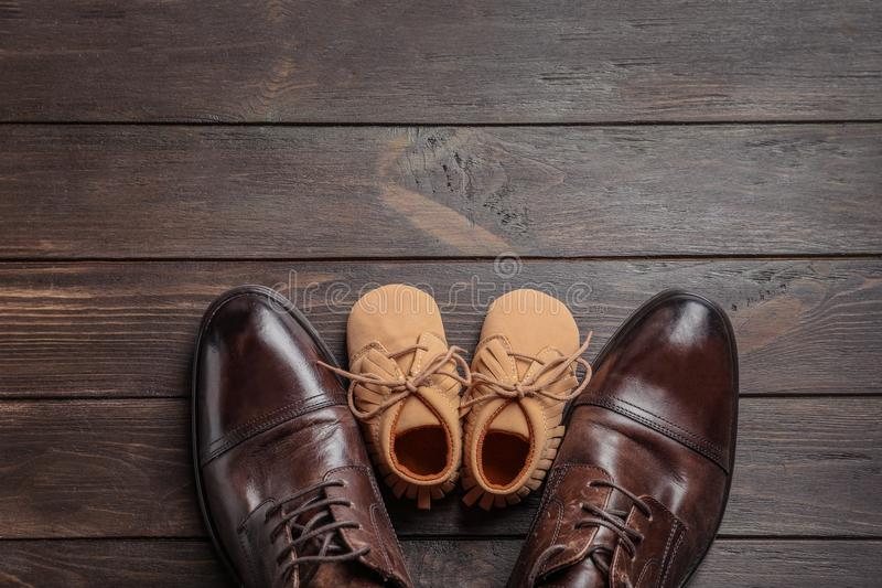 Flat lay composition with big and small shoes stock photography