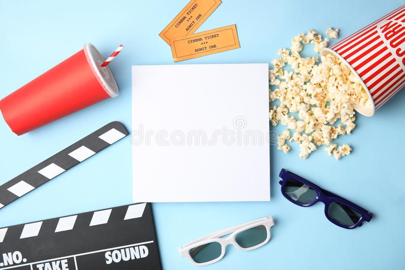 Flat lay composition with blank paper, popcorn and clapper on color background, mockup for design. Watching cinema royalty free stock image