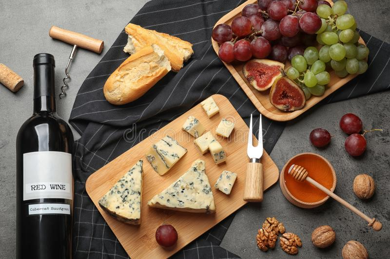 FLat lay composition with board of  blue cheese and wine on stone background. FLat lay composition with board of delicious blue cheese and wine on stone stock images
