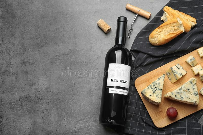 FLat lay composition with board of delicious blue cheese and wine on stone background. Space for text royalty free stock photos