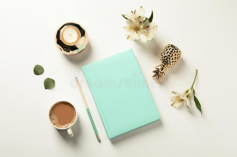 Flat lay composition with book, cup of coffee and decor elements. On white background royalty free stock photography