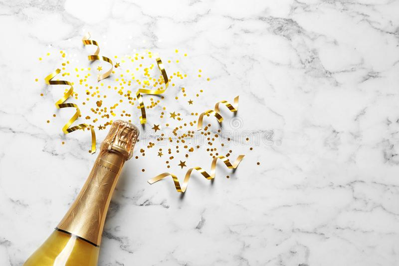 Flat lay composition with bottle of champagne for celebration on white marble background. Space for text royalty free stock photo