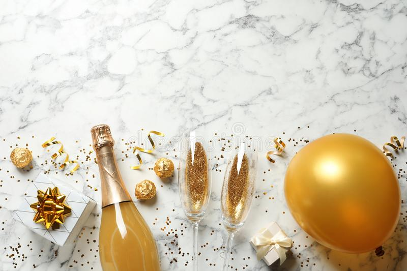 Flat lay composition with bottle of champagne for celebration on white marble background. Space for text royalty free stock images