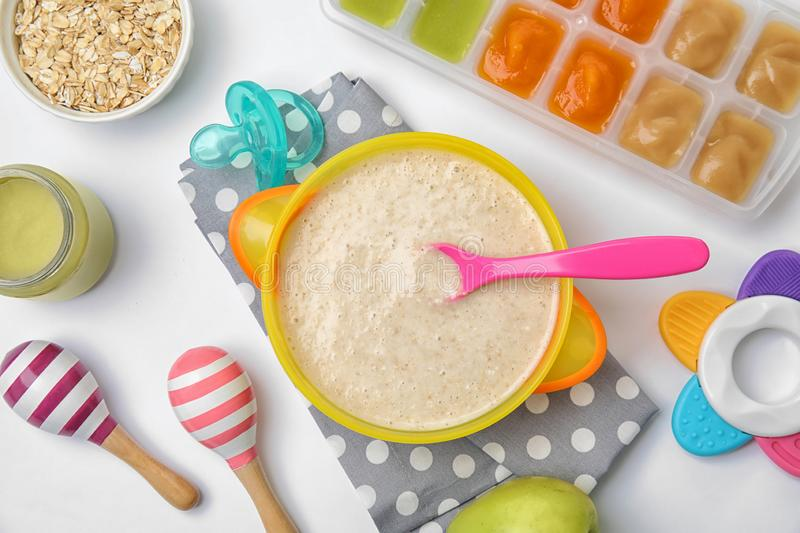 Flat lay composition with bowl of healthy baby food. On white background royalty free stock image