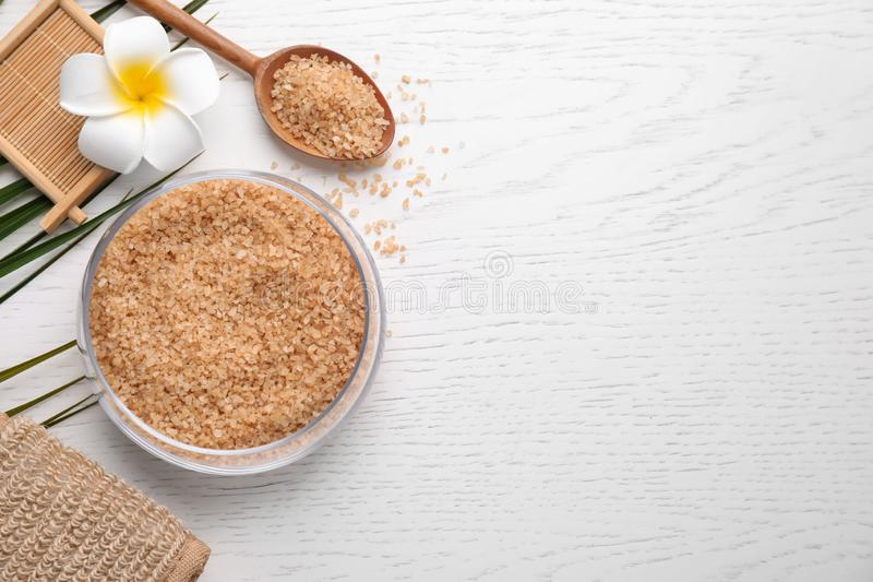 Flat lay composition with brown sea salt on white wooden background. Spa treatment. Flat lay composition with brown sea salt on white wooden background, space royalty free stock photography