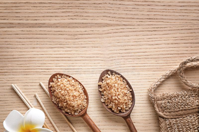 Flat lay composition with brown sea salt on wooden background. Spa treatment. Flat lay composition with brown sea salt on wooden background, space for text. Spa royalty free stock images