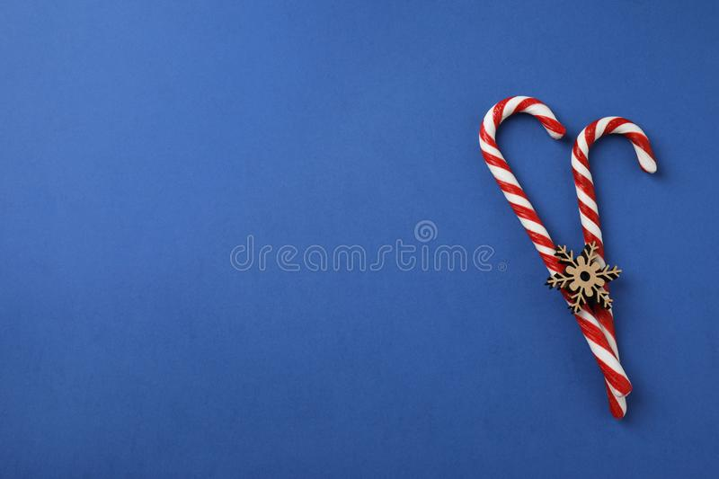 Flat lay composition with candy canes and snowflake on blue background. Space for text royalty free stock photos