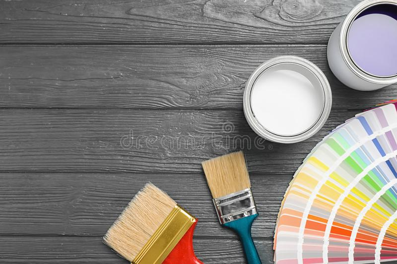 Flat lay composition with cans of paint, brushes and palette on grey wooden background stock photos