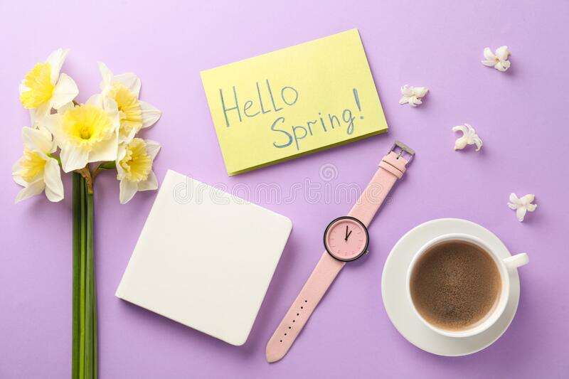 Flat lay composition of card with words HELLO SPRING and fresh flowers on violet background. Flat lay composition of card with words HELLO SPRING and fresh royalty free stock image
