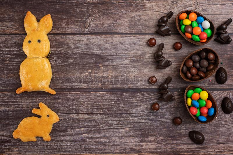 Flat lay composition with Chocolate Easter eggs, rabbit and sweets on dark wooden background. Top view. With copy space royalty free stock images