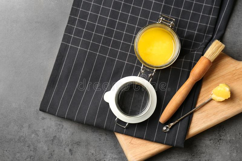 Flat lay composition with clarified butter and basting brush on grey background. Space for text royalty free stock photo