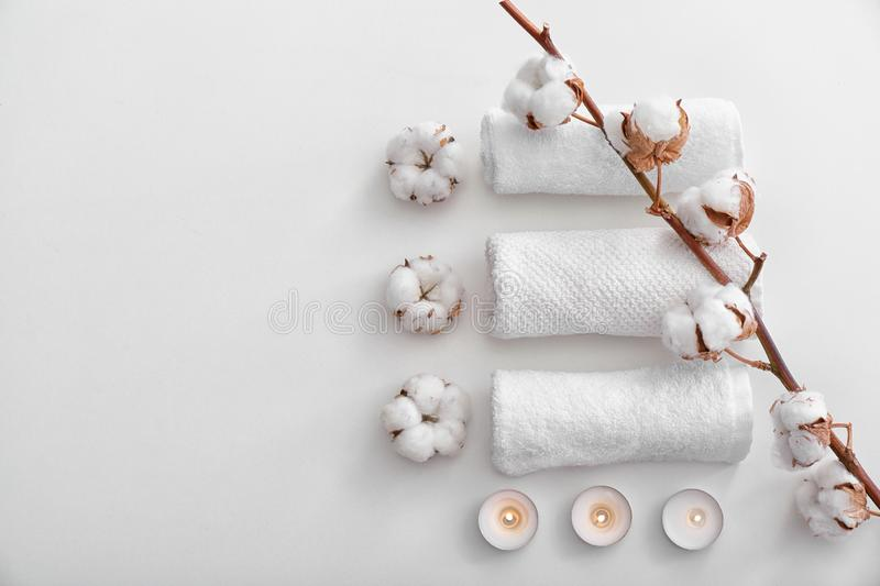 Flat lay composition with clean towels, burning candles and cotton flowers on white background royalty free stock photography