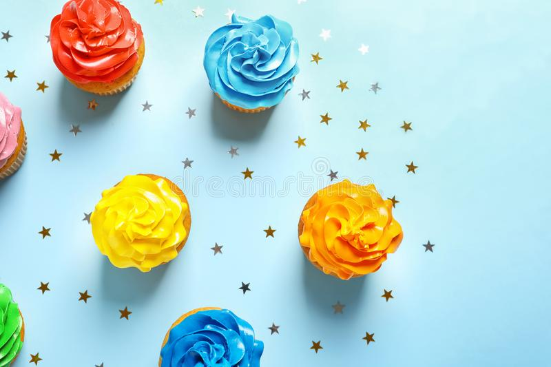 Flat lay composition with colorful birthday cupcakes. On color background royalty free stock images