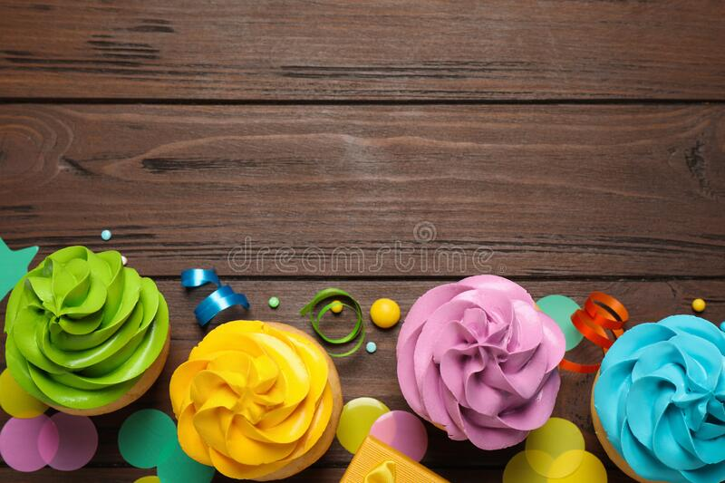 Flat lay composition with colorful birthday cupcakes on table. Space for text royalty free stock photos
