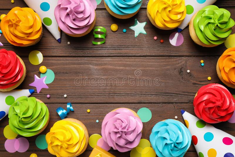Flat lay composition with colorful birthday cupcakes on table. Space for text stock photography