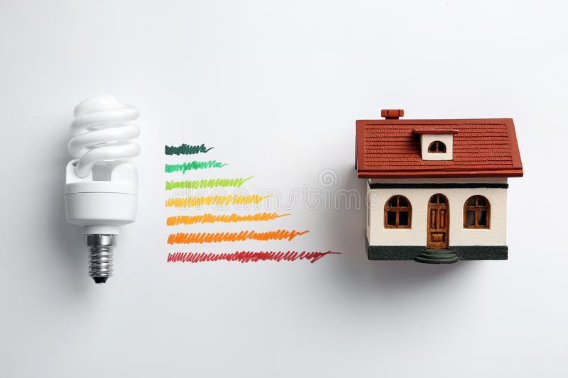 Flat lay composition with colorful chart, house model and lamp bulb on white background. Energy efficiency concept stock photography
