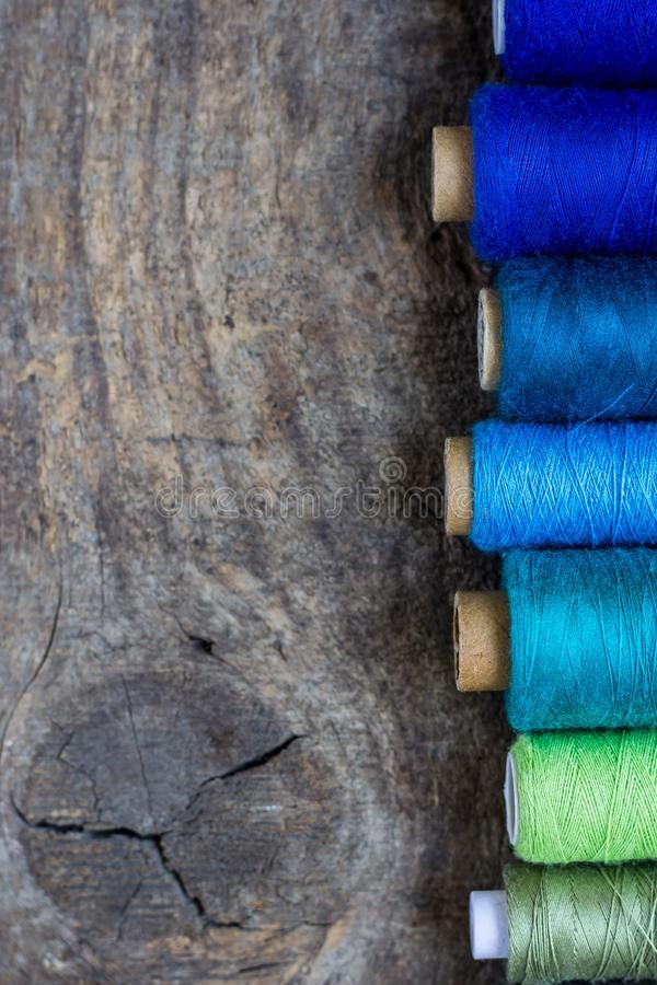 Flat lay composition with colorful sewing threads on wooden background. Fashion concept. Copy space. Flat lay composition with colorful sewing threads on wooden royalty free stock photos