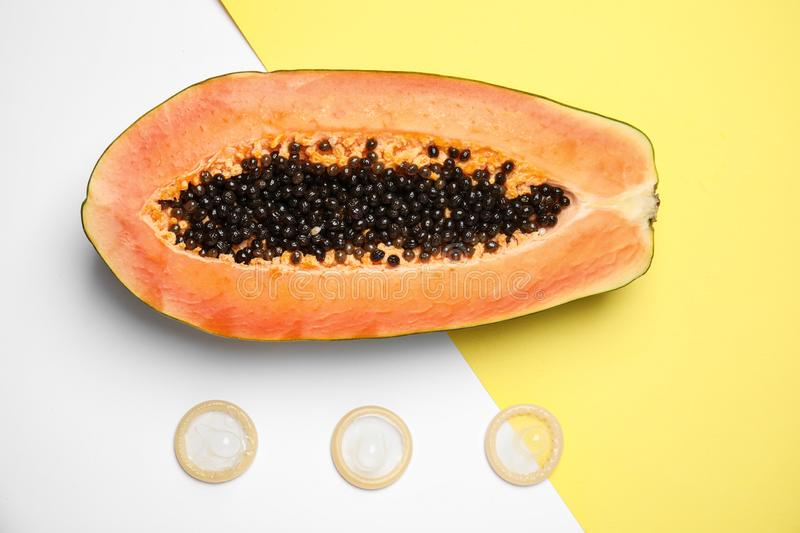Flat lay composition with condoms and papaya on color background. Erotic. Concept stock photo