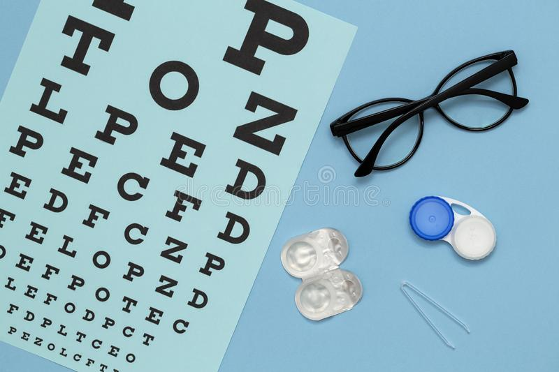 Flat lay composition with contact lenses, glasses and accessories on blue background. royalty free stock photo