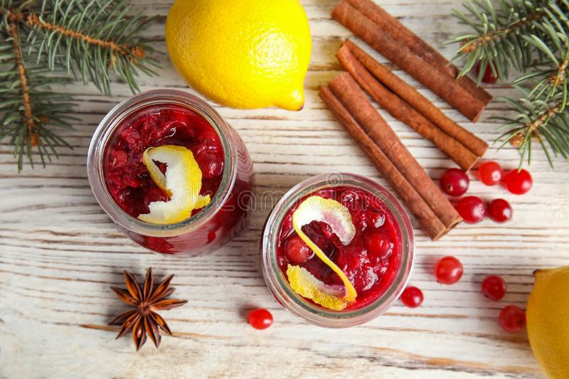 Flat lay composition with cranberry sauce in jars on white wooden. Background royalty free stock photos