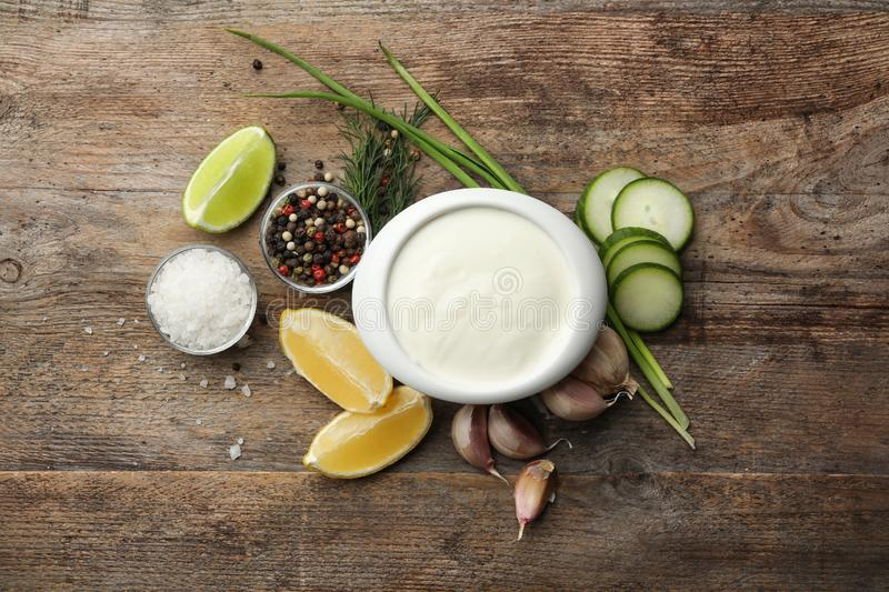 Flat lay composition with cucumber sauce and ingredients. On wooden background royalty free stock image