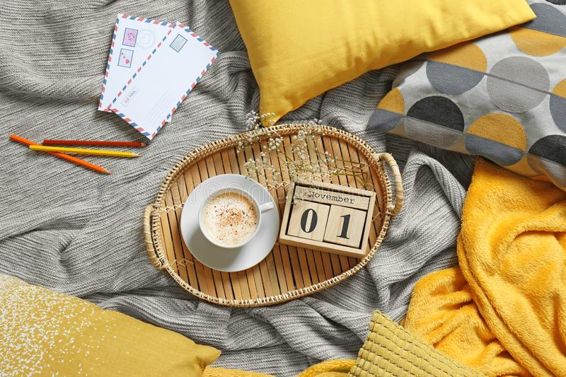 Flat lay composition with cup of , wooden block calendar, pillows and plaid on bed royalty free stock images