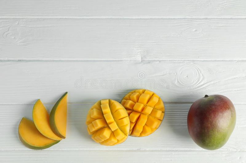 Flat lay composition with cut ripe mangoes on white background royalty free stock photo