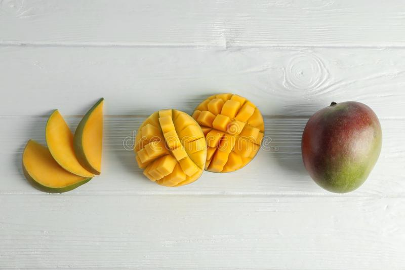 Flat lay composition with cut ripe mangoes on white background royalty free stock photography
