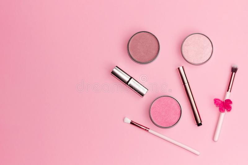 Flat lay composition with decorative makeup products on pastel pink background. royalty free stock photo