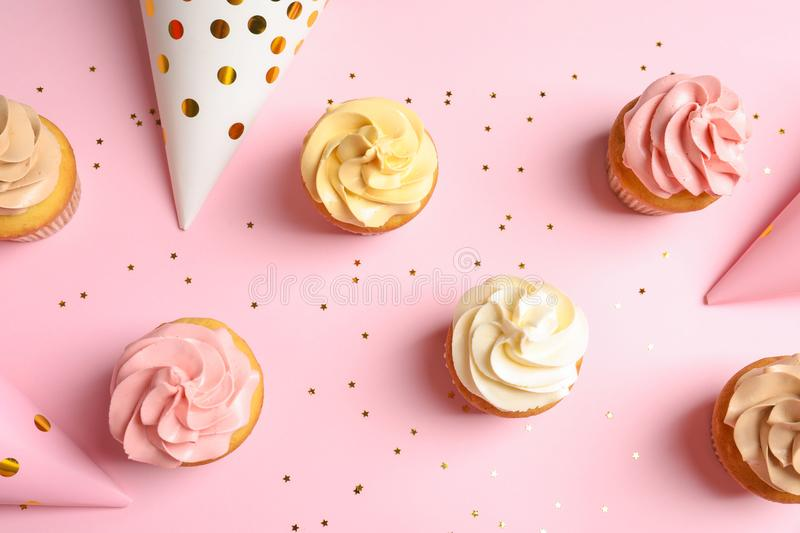 Flat lay composition with delicious birthday cupcakes. On color background stock photography