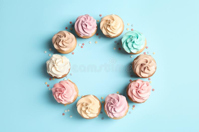Flat lay composition with delicious birthday cupcakes. And space for text on color background stock image