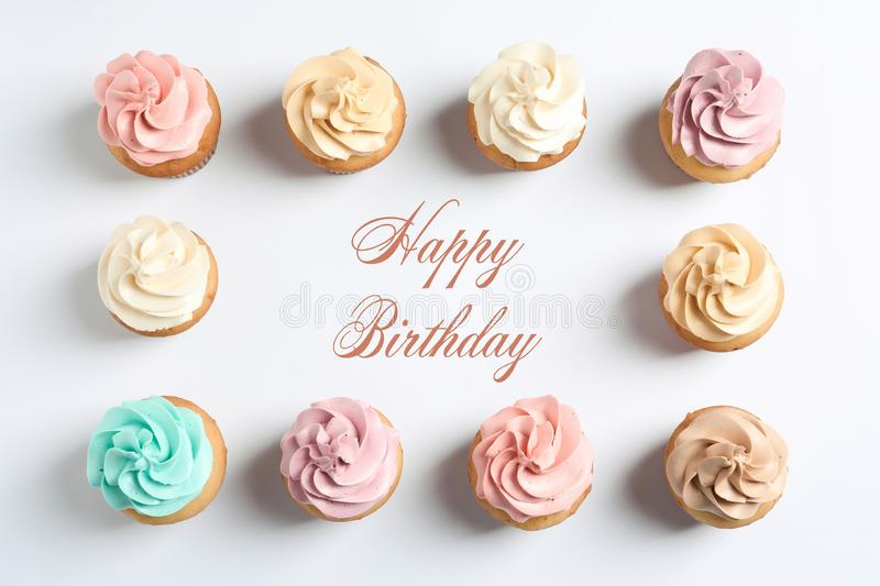 Flat lay composition with delicious birthday cupcakes and space for text. On white background stock photo