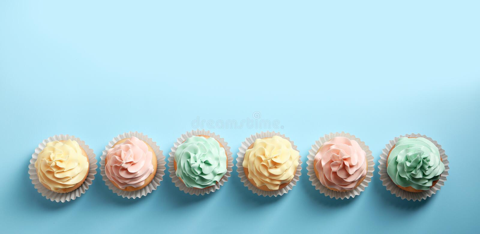 Flat lay composition with delicious cupcakes on color background. Space for text stock images