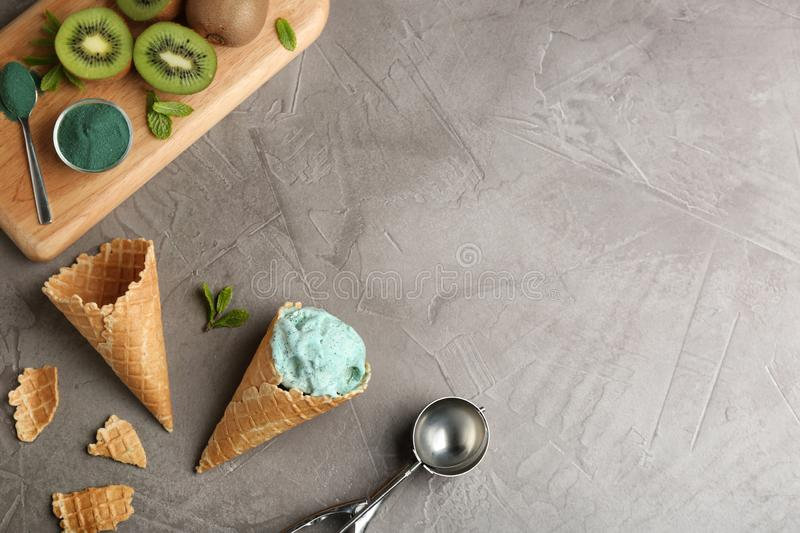 Flat lay composition with delicious spirulina ice cream cones and scoop on grey background. royalty free stock image