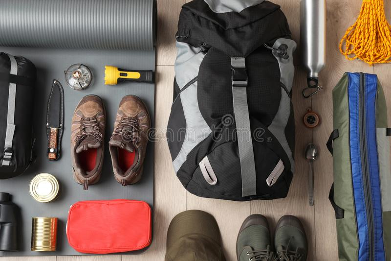 Flat lay composition with different camping equipment. On wooden background stock photo