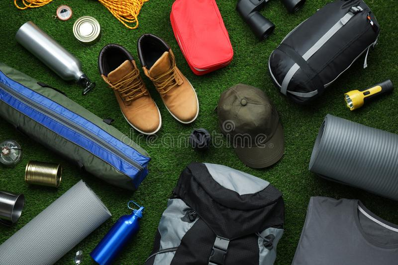 Flat lay composition with different camping equipment. On green grass stock images